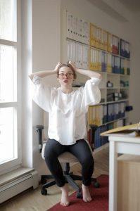 Жена на работа държи с ръце главата си притеснена от това което се е сетила