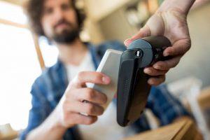 момче плаща на ПОС терминал с телефона